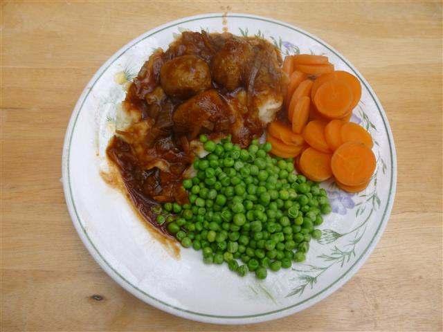 Meatballs in onion gravy with mash, peas & carrots